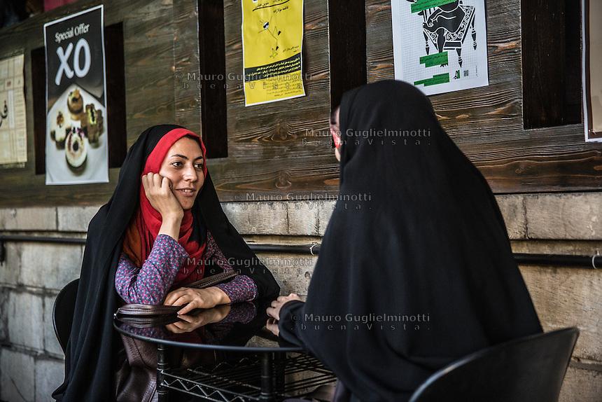 due ragazze velate sedute al bar <br /> two girls discussing in a bar