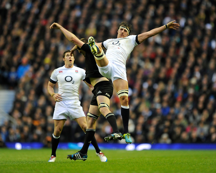 Tom Wood of England jumps for the high ball against Brodie Retallick of New Zealand during the QBE Autumn International match between England and New Zealand at Twickenham on Saturday 16th November 2013 (Photo by Rob Munro)