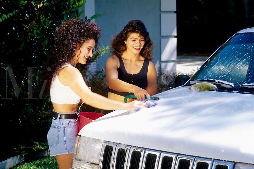 Affluent lesbian couple having fun while washing their sport-utility vehicle car at their hom