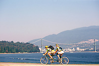 Stanley Park, Vancouver, BC, British Columbia, Canada - Couple cycling on Tandem Bike on Seawall along Burrard Inlet in Summer - Lions Gate Bridge, West Vancouver, and North Shore Mountains in background