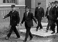 Palais de Justice. 4 octobre 1971. Vue d'ensemble de l'arrivée des accusés : vue de 3/4 face de René Vignal menotté à un policier ; derrière un autre accusé suit entouré de policiers. Cliché pris lors du procès de René Vignal (ancien footballeur), accusé d'une série de braquages perpétués à Toulouse et dans la région bordelaise entre 1969 et 1970. Observation: Au côté de René Vignal, comparaissaient également MM. Francis Bataille, Roger Claverie, Roger Martin, Marcel Filiol, Jean-Pierre Arrou, Guy Martin, René Doncel et Jean-Louis Parrenin.