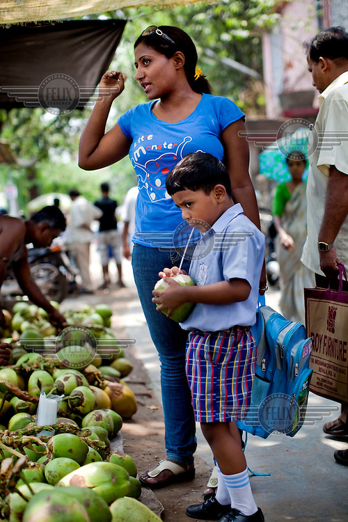 Razia Shabnam (in blue) buys coconut juice with her son, Saihaan, after picking him up from the St. Thomas School in Kidderpur. 28 year old Razia Shabnam was one of the first women boxers in Kolkata and also the first woman in her community to go to college. She is now a coach and one of only three international female boxing referees in India.