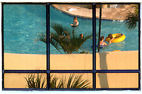 A hotel pool is reflected in a hotel window at Virginia Beach, Va.