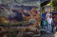 Armenia. Yerevan. An Armenian family stands in the amusement park located in the city center. Shooting range at amusement park arcade. On the outside wall, a picture with two hunters shooting their rifles. Yerevan, sometimes spelled Erevan, is the capital and largest city of Armenia. 1.10.2019 © 2019 Didier Ruef