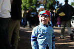 18 October 2009: A young spectator dressed as a jockey watches as some of his idols head back into the jockey's quarters to get changed for the next race.