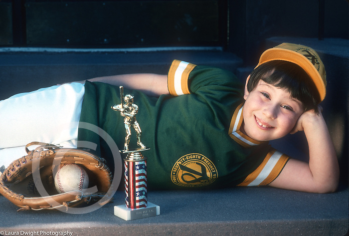 portrait of 6 year old girl in softball uniform posing proudly with participation trophy glove and ball