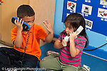 Education preschool 4 year olds boy and girl pretend play talking on telephones side by side horizontal looking at each other