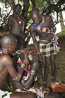 Ethiopia. Southern Nations, Nationalities, and Peoples' Region. Omo Valley. Turmi. Hamar tribe (also spelled Hamer). Pastoralist group. Ritual for a young man before the traditional cattle jumping ceremony. A Hamar man comes of age by leaping over a line of cattle. The bull jumping ceremony is one of the most important in man's life and once completed allows him to marry, own cattle and have children. The ceremony is about hierarchy and tribe's membership. The young man who is to leap has his head parially shaved and he's rubbed with sand to wash away his sins. He's then smeared with dung to give him strength while strips of tree bark are strapped around his naked body in a cross as a form of spiritual protection. The elders line up between six, like in the picture, and up to twenty cows and castrated male cattle (depending on family's wealth). The young man underwent a number of rituals before he leaps onto and runs rapidly over a series of cattle held by other men. To come of age, the man must leap across the line a minimum of four times. Only when, without falling, he has been through his initiation rite can he marry the wife chosen for him by his family, and start to build up his own herd. The Omo Valley, situated in Africa's Great Rift Valley, is home to an estimated 200,000 indigenous peoples who have lived there for millennia. Amongst them are 60'000 to 70'000 Hamar, an Omotic community inhabiting southwestern Ethiopia. They live in Hamer woreda (or district), a fertile part of the Omo River valley, in the Debub Omo Zone of the Southern Nations, Nationalities, and Peoples Region (often abbreviated as SNNPR) which is one of the nine ethnic divisions of Ethiopia. 9.11.15 © 2015 Didier Ruef