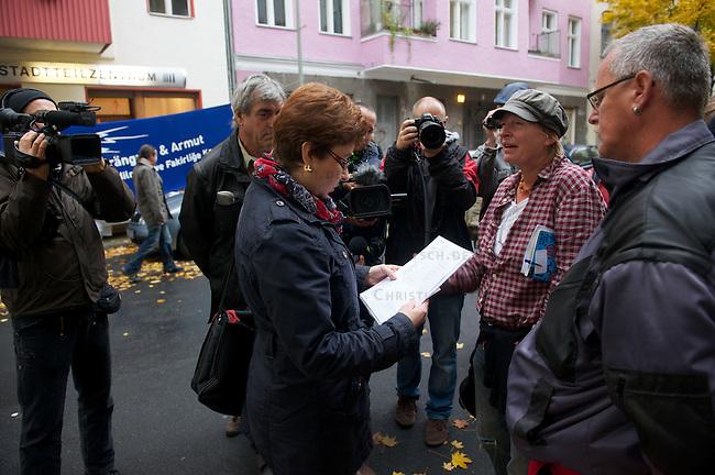Am Morgen des 22. Oktober 2012 verhinderten ca. 60 Menschen die zwangsweise Raeumung einer 5-koepfigen Familie aus ihrer Wohnung in Berlin-Kreuzberg. Sie versperrten mit einer Sitzblockade den Zugang zum Haus in der Lausitzerstrasse 8. Der Vermieter hatte die Zwangsraeumung der Familie gerichtlich beantragt, da die Mieterhoehung angeblich erst nach Ablauf einer gesetzten Frist gezahlt worden sein soll. Die Gerichtsvollzieherin musste unverrichteter Dinge wieder gehen. Als Begruendung fuer die Nicht-Volllstreckung behauptete sie wahrheitswidrig, es habe Ausschreitungen gegeben.<br /> Im Bild: Die Gerichtsvollzieherin mit dem Raeumungstitel begleitet von zwei Handwerkern wird von einer Anwohnerin (mit Muetze) gebeten, auf die Raeumung zu verzichten.<br /> 22.10.2012, Berlin<br /> Copyright: Christian-Ditsch.de<br /> [Inhaltsveraendernde Manipulation des Fotos nur nach ausdruecklicher Genehmigung des Fotografen. Vereinbarungen ueber Abtretung von Persoenlichkeitsrechten/Model Release der abgebildeten Person/Personen liegen nicht vor. NO MODEL RELEASE! Nur fuer Redaktionelle Zwecke. Don't publish without copyright Christian-Ditsch.de, Veroeffentlichung nur mit Fotografennennung, sowie gegen Honorar, MwSt. und Beleg. Konto: I N G - D i B a, IBAN DE58500105175400192269, BIC INGDDEFFXXX, Kontakt: post@christian-ditsch.de<br /> Bei der Bearbeitung der Dateiinformationen darf die Urheberkennzeichnung in den EXIF- und  IPTC-Daten nicht entfernt werden, diese sind in digitalen Medien nach §95c UrhG rechtlich geschuetzt. Der Urhebervermerk wird gemaess §13 UrhG verlangt.]