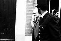 """Picard, Me Cathala, Me Bouscatel, Me Rastoul"""". 14 rue d'Aubuisson. 30 novembre 1976. Plan taille de profil de Claude Birague sortant de chez lui, à côté de lui un policier. Cliché pris le jour d'une reconstitution judiciaire dans le cadre de l'affaire du meurtre de René Trouvé. Observation: Affaire René Trouvé-Birague : le 19 février 1976, le journaliste René Trouvé est assassiné d'une balle dans la tête, par deux inconnus, alors qu'il regagne son domicile au 33 rue Bayard."""