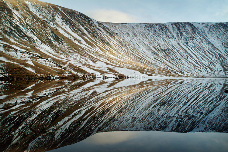 Snow covered hills reflect into the still water of a lake. The Lake District.