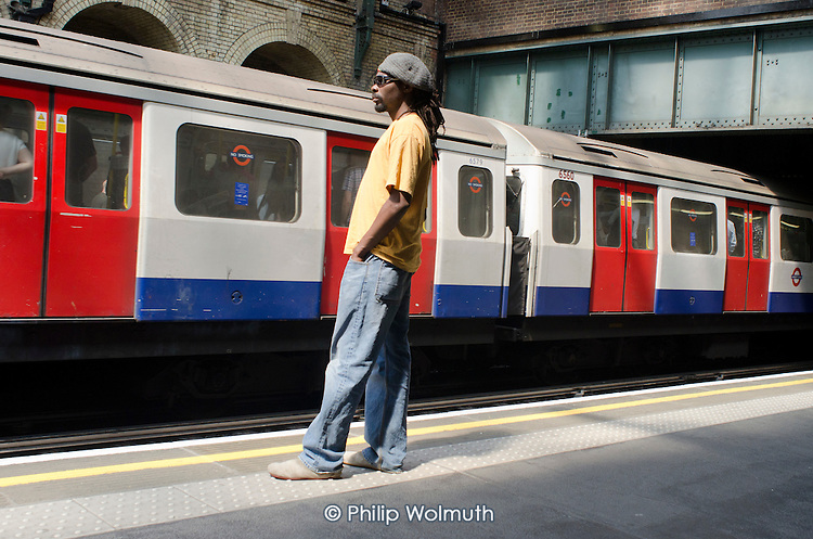 A man waits on the platform at Notting Hill tube station.