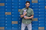 """© Joel Goodman - 07973 332324 - all rights reserved . 12/01/2020 . Salford , UK . KAYNE LEWIS (25) in front of post boxes on the ground floor foyer of the block of his rented flat , which he shares with CHASE  (the 5 month old Chihuahua) and some fish , in apartment block """"Duet"""" , on Salford Quays in Greater Manchester . Photo credit : Joel Goodman"""