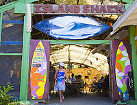 Woman walking out of the Island Shack eatery near Rocky Point on the North Shore of Oahu