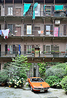 The exterior of an apartment block with balconies. Plant pots are placed either side of the main entrance.