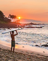 At sunset, a surfer holds his board over his head after surfing as looks out over the ocean, North Shore, O'ahu.