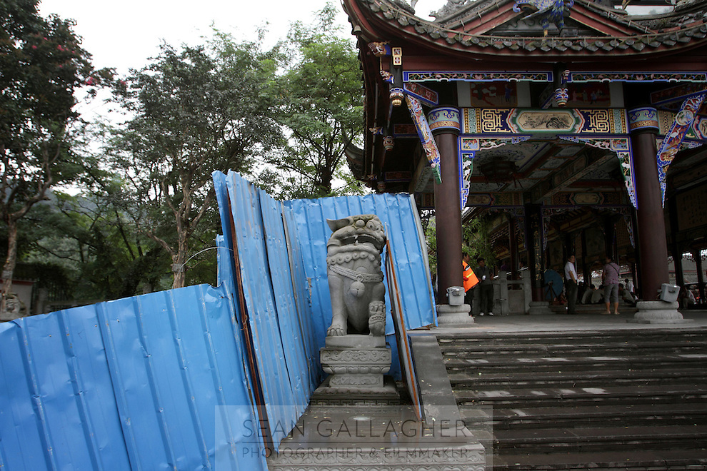 """A stone lion outside the entrance to the Dujiangyan Irrigation System. The system is regarded as an """"ancient Chinese engineering marvel."""" By naturally channeling water from the Min River during times of flood, the irrigation system served to protect the local area from flooding and provide water to the Chengdu basin. Sichuan Province. 2010"""