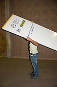 """A man carries a panel marked """"Cabinet of the Presidency of Brazil"""" during the build-up at the Rio Centre. United Nations Conference on Sustainable Development (Rio+20), Rio de Janeiro, Brazil. Photo © Sue Cunningham."""