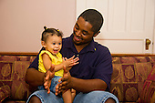 MR / Schenectady, NY. Father (22, African American) encourages his infant daughter (girl, 10 months, African American & Caucasian) to imitate him by clapping hands. MR: Dal7, Dal4. ID: AL-HD. © Ellen B. Senisi