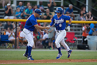 Ben Johnson (6) of the Burlington Royals shakes hands with third base coach Scott Thorman (16) as he rounds the bases after hitting a home run against the Greeneville Astros at Burlington Athletic Park on August 29, 2015 in Burlington, North Carolina.  The Royals defeated the Astros 3-1. (Brian Westerholt/Four Seam Images)