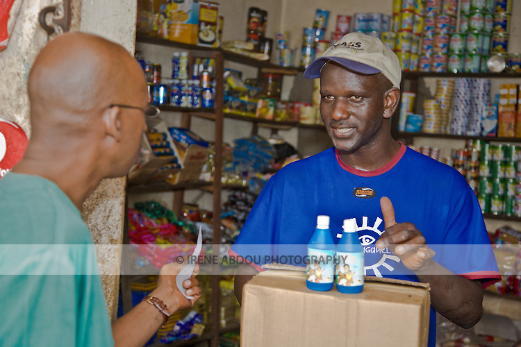"""A wholesaler in Conakry, Guinea tells a customer about """"Sur'Eau,"""" a chlorine product that makes water safe to drink.  Sur'Eau is distributed by the international social marketing organization, Population Services International."""