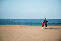A mother and child take a stroll along the beach at Tenby, Pembrokeshire, Wales, UK