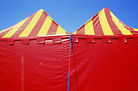 Red and yellow circus tents on blue sky