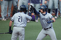 Brock Gagliardi (10) of the Old Dominion Monarchs high fives teammate Matt Coutney (21) after hitting a home run against the Charlotte 49ers at Hayes Stadium on April 23, 2021 in Charlotte, North Carolina. (Brian Westerholt/Four Seam Images)