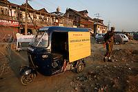 The rickshaw of Farooq Abdullah News Agency parked in Srinagar. Indian soldier strolling by. Kashmir, India. © Fredrik Naumann/Felix Features