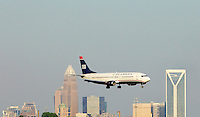 A US Airways plane makes its descent at Charlotte-Douglas International Airport in Charlotte, North Carolina. The downtown Charlotte skyline is in the background. Charlotte-based photographer has other images of transportation, airplanes on runways (and taking off and landing) and interior/exterior airport images of Charlotte-Douglas Intl Airport in portfolio.