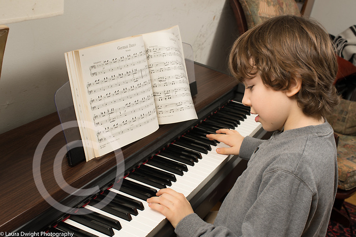 8 year old boy at home playing musical instrument piano