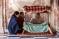 India, Dehradun.  Woman Reading Sacred Scripture to Two Visitors at the Entrance to the Inner Shrine of the Sikh Temple Durbar Shri Guru Ram Rai Ji Maharaj, built in 1707.