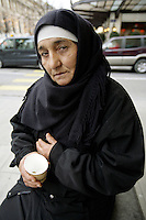 Switzerland. Geneva. Poverty in Geneva. A muslim woman from Bosnia is begging for money in the center of the town. As a moslem woman, she is dressed in black clothes and wears a veil on her head. © 2005 Didier Ruef