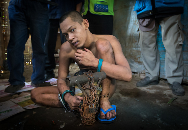 """5 April 2017, Surabaya,East Java,Indonesia: Febrianto, a 24 year old mental illness sufferer prepares to be released from the chains he has been shackled to a stake for the past two years in a goat shed next to his family in Pehwetan village, East Java. Indonesian Social Affairs Dept. workers cut the bonds and wash his emaciated body and apply first aid before putting him in a straight jacket and taking him to a facility in Malang for treatment. Febrianto is a patient in a program called """"E- Shackling"""" which aims to free people suffering from mental illness, from the shackles that family often place them in to control them in the wake of a lack of treatment options and which will treat them and enter them in a data base allowing them to be traced before releasing them back to their families. Some people stay chained to a stake or in rooms for years by their families and not all families are willing to take their sick family members back. Picture by Graham Crouch/The Australian"""