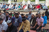 South Africa, Cape Town, District Six.  Overflow Crowd Prays in the Courtyard of Al-Azhar Mosque for Noon Friday Prayers.  Note that most are of South Asian origin.