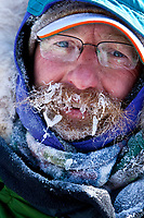 Portait of Ross Adam frosted up as he arrives in Rohn during the 2010 Iditarod