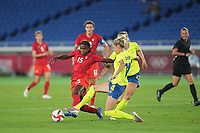 YOKOHAMA, JAPAN - AUGUST 6: Nichelle Prince #15 of Canada battles for the ball with Nathalie Bjorn #14 of Sweden during a game between Canada and Sweden at International Stadium Yokohama on August 6, 2021 in Yokohama, Japan.
