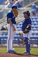 Toronto Blue Jays pitcher Nate Pearson (24) talks with catcher Alejandro Kirk (30) during a Major League Spring Training game against the Pittsburgh Pirates on March 1, 2021 at TD Ballpark in Dunedin, Florida.  (Mike Janes/Four Seam Images)