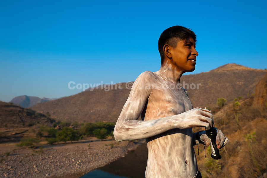 """A Cora Indian boy, painting his body, prepares himself for the religious ritual celebration of Semana Santa (Holy Week) in Jesús María, Nayarit, Mexico, 21 April 2011. The annual week-long Easter festivity (called """"La Judea""""), performed in the rugged mountain country of Sierra del Nayar, merges indigenous tradition (agricultural cycle and the regeneration of life worshipping) and animistic beliefs with the Christian dogma. Each year in the spring, the Cora villages are taken over by hundreds of wildly running men. Painted all over their semi-naked bodies, fighting ritual battles with wooden swords and dancing crazily, they perform demons (the evil) that metaphorically chase Jesus Christ, kill him, but finally fail due to his resurrection. La Judea, the Holy Week sacred spectacle, represents the most truthful expression of the Coras' culture, religiosity and identity."""