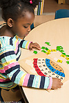 Education preschool 3-4 year olds girl working on alphabet and number wooden puzzle in turtle shape