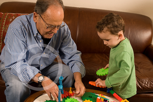 Grandfather in his early 80s playing with plastic interlocking gear toy and his 3 year old grandson horizontal Caucasian