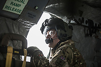 An air crew member  looks out the window of a British Merlin helicopter during practice in the Arctic, over the terrain near Bardufoss, Norway. <br /> <br /> In 2019 the Arctic exercise Clockwork passed 50 years of training in Norway, and now has a permanent base within the Norwegian Air Force base at Bardufoss. <br /> <br /> 845 Naval Air Squadron is a squadron of the Royal Navy's Fleet Air Arm. Part of the Commando Helicopter Force, it is a specialist amphibious unit operating the Leonardo Commando Merlin Mk3 helicopter and provides troop transport and load lifting support to 3 Commando Brigade Royal Marines.<br /> <br /> ©Fredrik Naumann/Felix Features