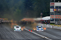 Aug. 6, 2011; Kent, WA, USA; NHRA funny car driver Tim Wilkerson (right) races alongside Mike Neff during qualifying for the Northwest Nationals at Pacific Raceways. Mandatory Credit: Mark J. Rebilas-