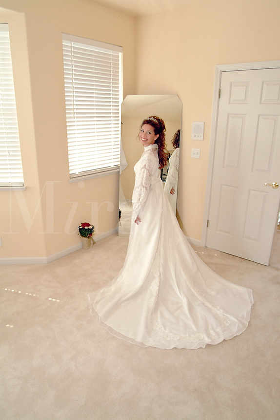 Bride trying on her mothers wedding dress.