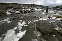 01/02/14<br /> <br /> A walker crosses the frozen Kinder river high up in the Derbyshire Peak District.  <br /> <br /> F Stop Press.  www.fstoppress.com. Tel: +44 (0)1335 300098