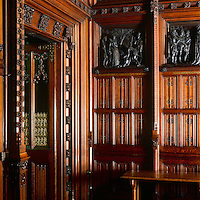 Wood panelling, elaborately carved with flower motifs, clads the Prince's Chamber. The polished wood also frames historically themed bronze reliefs by William Theed