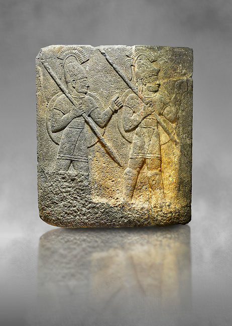 Hittite relief sculpted orthostat stone panel of Herald's Wall. Limestone, Karkamıs, (Kargamıs), Carchemish (Karkemish), 900-700 B.C. Military parade. Anatolian Civilisations Museum, Ankara, Turkey.<br /> <br /> Three helmeted soldiers in short skirts carry the shield on their backs and the spears in their hands. The bottom right part of the relief was left untreated since the pedestal stood in front of it. <br /> <br /> Against a grey art background.