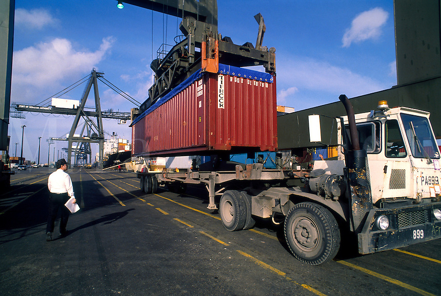 A crane loads a cargo container onto a truck.
