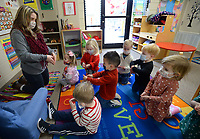 Rosa Marinoni, a teacher at First United Presbyterian Church's First School, shows her preschool students how to make a heart shape with their hands Friday, Feb. 12, 2021, during a Valentine's Day party at the school in Fayetteville. Students enjoyed a sweet snack before making cards for their parents for Valentine's Day, which is Sunday Visit nwaonline.com/210213Daily/ for today's photo gallery. <br /> (NWA Democrat-Gazette/Andy Shupe)