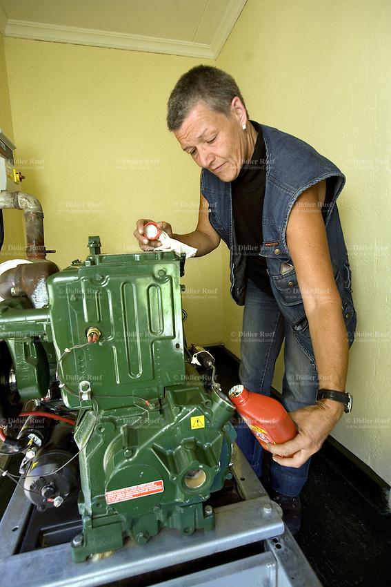 Kenya. Rift Valley province. Thugunui ( 45 km from Nakuru). Ruth Schäfer, a swiss citizen, adds oil to a generator at the Rhein-Valley water pump project. A swiss non-governmental organization (NGO) runs the Rhein-Valley program. © 2008 Didier Ruef